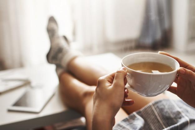 tasse-the-froid-femme-allongee-canape-tenant-jambes-table-basse-buvant-du-cafe-chaud-appreciant-matin-etant-humeur-reveuse-detendue-fille-chemise-surdimens